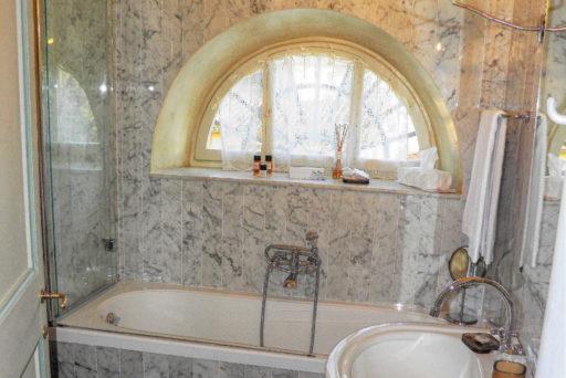 Una luminosa finestra ad arco illumina un'elegante servizio con vasca da bagno, lavandino e bidet.